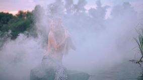 Mermaid at sunset, in the fog, along the middle of the river, playing with hair. A beautiful mysterious mermaid with a silver tail sits on a stone in the water stock video