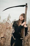 Beautiful mysterious mystical girl with long hair in black dress holding a braid in dark autumn forest on the way. Mystical pretty Stock Photography
