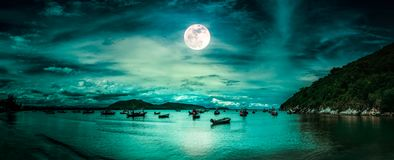Beautiful mysterious nature landscape. Beach by the sea with mountains and full moon at nighttime. Beautiful panorama nature landscape. Beach by the sea with stock photos