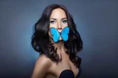 Beautiful mysterious woman with butterflies blue color on her face, brunette and paper artificial blue butterflies on the girls royalty free stock images