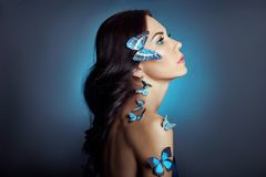 Beautiful mysterious woman with butterflies blue color on her face, brunette and paper artificial blue butterflies on the girls royalty free stock photos