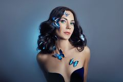 Beautiful mysterious woman with butterflies blue color on her face, brunette and paper artificial blue butterflies on the girls royalty free stock photo