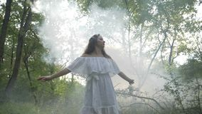 Beautiful mysterious woman dancing in the fog in the forest - stock video
