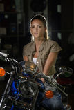 Beautiful mysterious woman in light sitting on her chopper motorcycle. Beautiful and charming, fashionable brunette woman sitting on a cool blue motorcycle Stock Photo