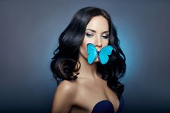 Free Beautiful Mysterious Woman With Butterflies Blue Color On Her Face, Brunette And Paper Artificial Blue Butterflies On The Girls Stock Images - 130623604