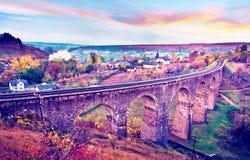 Beautiful mystical autumn landscape with ancient viaduct and railroad track at sunset. Plebanivka, Ternopil region, Ukraine. stock image