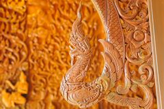 Beautiful Naga teak wood carving sculptures in Thai temple. Stock Photo