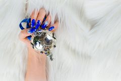 Beautiful nail decorations for your Christmas and New Year parti. Nails decorated with blue color and bright stars to celebrate Christmas and the last of the Stock Photos