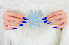 Beautiful nail decorations for your Christmas and New Year parti. Nails decorated with blue color and bright stars to celebrate Christmas and the last of the Stock Photo