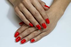 Beautiful nails are covered with red gel lacquer. Woman in a beauty salon stock images