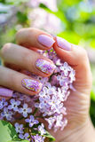 Beautiful nails with lilac flowers and fresh flowers Royalty Free Stock Photography