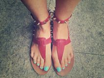 Beautiful nails and red sandals. Beautiful nails with and sandals with spikes Stock Photos