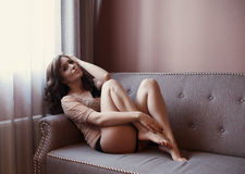 Beautiful naked brunette lying on the sofa Royalty Free Stock Photography