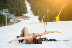 Beautiful naked female skier is lying on snowy slope near ski lift at  resort Stock Photography