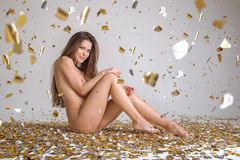 Beautiful Naked Woman Celebrating Posing Isolated On Gray Background Surrounded Falling Golden Confetti Stock Image