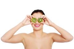 Beautiful naked woman with kiwi fruit on eyes. Isolated on white Royalty Free Stock Photos