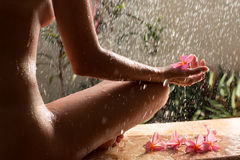 Beautiful naked woman sits under rain with flower Stock Photos