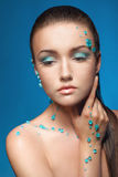 Beautiful naked young woman covered with blue crystals Royalty Free Stock Photography
