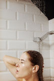 Beautiful naked young woman taking shower in bathroom Royalty Free Stock Photo