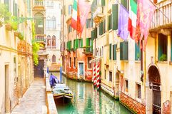 Beautiful narrow canal and street with boats, european union, venice and italian flags in Venice during summer day, Italy. royalty free stock photography