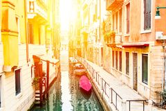Beautiful narrow canal and street with boats in Venice during summer day, Italy. stock photography