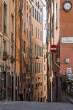 Beautiful narrow street in Genoa, Italy. Beautiful narrow street with high buildings and wall clock in Genoa, Italy Stock Photo