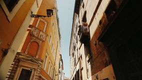 Beautiful narrow street in the old part of Rome, Italy. Medieval buildings covered with ivy. Steadicam wide lens shot stock footage