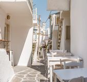 Narrow street with white houses, Greece. Beautiful narrow street with white houses in Mikonas island, Greece. Traditional narrow street with white facedes of Royalty Free Stock Images
