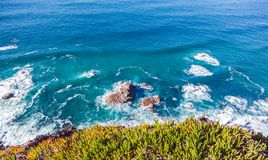 Beautiful natural abstract background, turquoise water and waves. Are broken against a stone. Cabo da Roca, Portugal. The power of the ocean Stock Photography