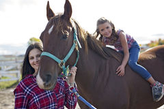 Beautiful and natural adult woman outdoors with horse child Royalty Free Stock Photo