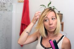 Beautiful natural blond girl using hair iron at home.  royalty free stock photos