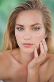 Beautiful natural blonde looking at camera with eye cream on Stock Photography