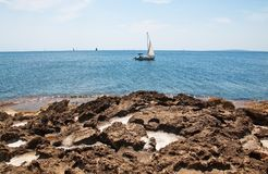 Beautiful natural coast landscape with salt cavities. In rocks and sailboat in turquoise blue water in Mallorca, Spain stock photography