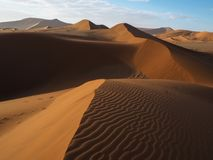 Beautiful natural curved ridge line and wind blow pattern of rusty red sand dune with shade and shadow on vast desert landscape Stock Images