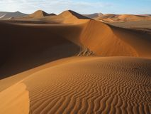 Beautiful natural curved ridge line and wind blow pattern of rusty red sand dune valley with shade and shadow on desert landscape Stock Photography