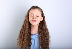 Beautiful natural expression laughing kid girl looking with long. Curly hair style on blue background Stock Photography