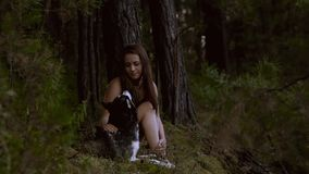 Beautiful natural girl sitting in the forest with her dog looking right into his eyes stock footage