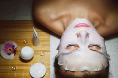 Beautiful natural girl woman in the spa salon, It makes a face mask royalty free stock photo
