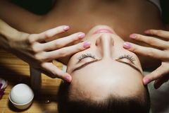 Beautiful natural girl woman in the spa salon, It makes a face mask. Beautiful natural girl woman in the spa salon, It makes a face massage, facial rejuvenation Stock Photos