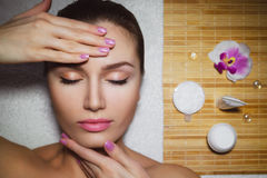 Beautiful natural girl woman in the spa salon, It makes a face mask. Beautiful natural girl woman in the spa salon, It makes a face massage, facial rejuvenation Stock Images