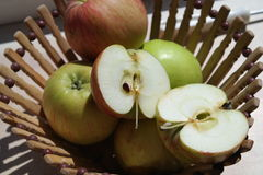 Beautiful natural juicy green and red apples in wooden basket on the nature Stock Photo