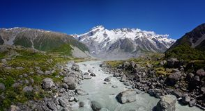 Hooker Valley Track, Mount Cook, New Zealand. Beautiful natural landscape. Rocks, river and snowy mountains in the background. Walking the Hooker Valley Track Royalty Free Stock Images