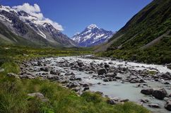 Hooker Valley Track, Mount Cook, New Zealand. Beautiful natural landscape. Rocks, river and snowy mountains in the background. Walking the Hooker Valley Track Royalty Free Stock Photo