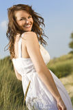 Beautiful Natural Laughter. A beautiful brunette model walking through tall grass illuminated by natural late evening golden sunshine laughing over her shoulder Royalty Free Stock Photography