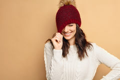 Beautiful natural looking young smiling brunette woman, wearing knitted scarf, covered with snow flakes. Snowing winter Royalty Free Stock Photography