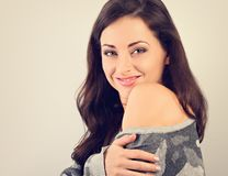 Beautiful natural makeup woman smiling with long hair style in warm winter sweater and hugging herself stock photo