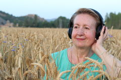 Beautiful Natural Mature Woman with Headphones Outdoors. Enjoying Music with Copy Space Stock Photography