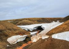 Beautiful natural phenomenon in Fjallabak Nature Reserve, Highlands of Iceland. Warm river flowing throw melting snow tunnel royalty free stock image