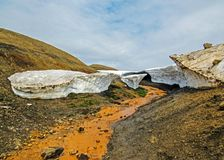 Warm river flowing throw melting snow tunnel in Jokultungur geothermal area. Laugavegur hiking route, Highland of Iceland, Europe royalty free stock photo