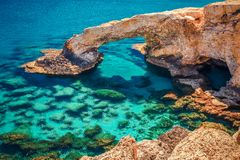 Beautiful natural rock arch near of Ayia Napa, Cavo Greco and Protaras on Cyprus island, Mediterranean Sea. Legendary bridge. Lovers. Amazing blue green sea and stock photography